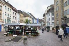 гражданское лицо и туристская покупка некоторый продукт в бакалейной лавке на улице среднего городка Цюриха старого Стоковые Фотографии RF