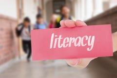 Грамотность против зрачков порции учителя в библиотеке стоковые изображения