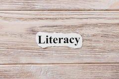 ГРАМОТНОСТЬ слова на бумаге Концепция Слова ГРАМОТНОСТИ на деревянной предпосылке стоковое фото rf