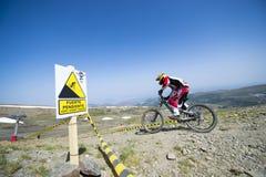 ГРАНАДА, ИСПАНИЯ - 30-ОЕ ИЮНЯ: Неизвестный гонщик на конкуренции велосипеда Bull горы покатого велосипед DH 2013 чашки, сьерра-нев Стоковые Изображения RF