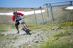 ГРАНАДА, ИСПАНИЯ - 30-ОЕ ИЮНЯ: Неизвестный гонщик на конкуренции велосипеда Bull горы покатого велосипед DH 2013 чашки, сьерра-нев Стоковое фото RF