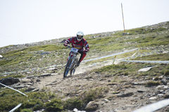 ГРАНАДА, ИСПАНИЯ - 30-ОЕ ИЮНЯ: Неизвестный гонщик на конкуренции велосипеда Bull горы покатого велосипед DH 2013 чашки, сьерра-нев Стоковая Фотография