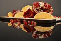 Гранатовое дерево и апельсин заклинивают на деревянной доске Стоковая Фотография