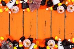 Граница двойника конфеты хеллоуина над старой оранжевой древесиной Стоковые Фото