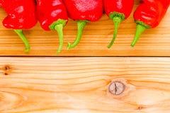 Граница накаленных докрасна перцев chili Кайенны на древесине Стоковая Фотография RF