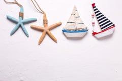 Граница от декоративных деревянных игрушек шлюпки и морских звёзд на tex Стоковое Фото