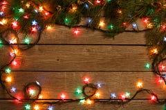 Граница светов рождества на деревянной предпосылке Стоковые Фото