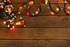 Граница светов рождества на деревянной предпосылке Стоковое Изображение