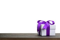 Граница с белой подарочной коробкой с фиолетовым смычком ленты стоковые изображения