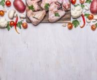 Граница с свежими сырцовыми крылами цыпленка на разделочной доске величает и картошки с томатами вишни красных перцев петрушки го Стоковое Фото