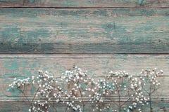 Граница чувствительных маленьких белых цветков на старой голубой предпосылке f Стоковая Фотография RF