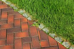 Граничьте край тротуара между лужайкой и тротуаром в парке стоковое изображение