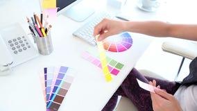 График-дизайнер смотря образцы цвета сток-видео