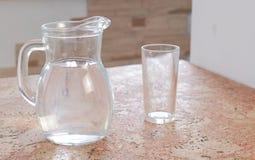 Графинчик с водой и пустым стеклом на таблице Стоковые Изображения RF