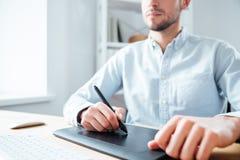 Графическая таблетка используемая серьезным дизайнером молодого человека в офисе Стоковое Изображение RF