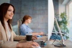 Графический дизайнер женщины на работе работая на компьютере для нового proje стоковое фото