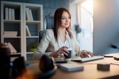 Графический дизайнер женщины на работе работая на компьютере для нового proj Стоковые Изображения RF