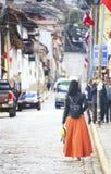 Графство Cusco, Перу - 8-ое августа 2018: Женщина нося оранжевую юбку и шляпу идет на steet в старом городке района Cusco внутри стоковая фотография rf