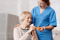 Грациозно превосходный доктор давая лекарство стоковые изображения