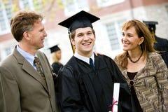 Градация: Студент-выпускник стоит с родителями Стоковое Изображение
