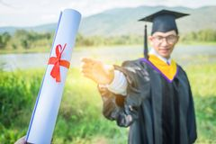 Градация: Студент стоя вверх и улыбка держа градацию cer стоковая фотография