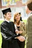 Градация: Учитель поздравляет нового студент-выпускника стоковое изображение