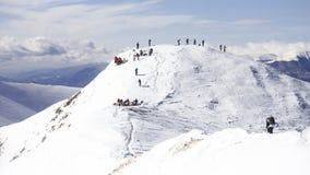Гребень горы Snowy с группами людей на верхней части Стоковые Изображения