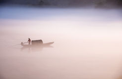 Гребля и удить на зоре Стоковые Фото