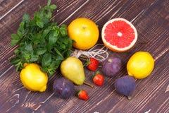Грейпфруты, груши, лимоны, смоквы, клубника, помело, мята на деревянной предпосылке; натюрморт с плодоовощами Стоковое фото RF
