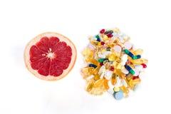Грейпфрут и пилюльки, дополнения витамина на белой предпосылке с космосом экземпляра, концепцией здорового питания Стоковые Фотографии RF