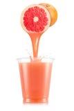 Грейпфрут моркови лить вне от плодоовощ в пластичную чашку Стоковое фото RF