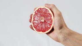 Грейпфрут, рука сжимает вне крупный план сока акции видеоматериалы