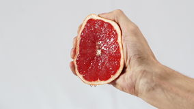Грейпфрут, рука сжимает вне крупный план сока сток-видео