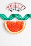 Грейпфрут с измеряя лентой на масштабе веса dieting Стоковая Фотография RF