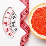Грейпфрут с измеряя лентой на масштабе веса dieting Стоковое фото RF