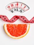 Грейпфрут с измеряя лентой на масштабе веса dieting Стоковое Изображение