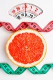 Грейпфрут с измеряя лентой на масштабе веса dieting Стоковое Изображение RF