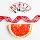 Грейпфрут с измеряя лентой на масштабе веса dieting Стоковое Фото