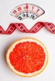 Грейпфрут с измеряя лентой на масштабе веса dieting Стоковые Изображения