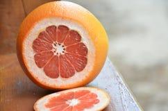 Грейпфрут с кусками на деревянном столе, предпосылке листвы Стоковая Фотография RF