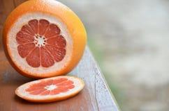Грейпфрут с кусками на деревянном столе, предпосылке листвы Стоковые Фотографии RF