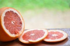 Грейпфрут с кусками на деревянном столе, предпосылке листвы Стоковая Фотография