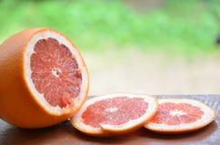 Грейпфрут с кусками на деревянном столе, предпосылке листвы Стоковое Фото