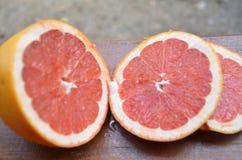 Грейпфрут с кусками на деревянном столе, предпосылке листвы Стоковые Изображения