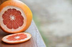 Грейпфрут с кусками на деревянном столе, предпосылке листвы Стоковые Фото