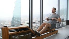 Грести к успеху Взгляд со стороны молодого человека в sportswear делая rowing перед окном на спортзале видеоматериал