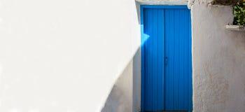 Греция, остров Kea Деревянная голубая дверь на белой предпосылке стены Стоковые Фотографии RF