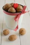 Грецкие орехи в белой чашке прыгнули вверх в красной тесемке Стоковые Фотографии RF