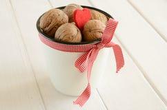 Грецкие орехи в белом ведре прыгнули вверх в красной тесемке Стоковое фото RF