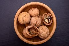Грецкие орехи в деревянной чашке на черной каменной предпосылке доски, космосе рамки для текста Стоковое фото RF